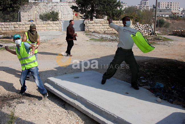 "A Palestinian demonstrators throw stones at Israeli soldiers during a protest in the Qalandia refugee camp, near the West Bank city of Ramallah, on November 9, 2009 to mark the 20th anniversary of the fall of the Berlin Wall in Germany. Palestinians are using the anniversary of the end of the Berlin wall to press their campaign against Israel's ""wall"", mostly a razor-wire fence interspersed with concrete barricades which Israel began building around the West Bank in 2002. The Jewish state has come under international censure for the barrier's de facto annexation of occupied West Bank land.. Photo by Issam Rimawi"