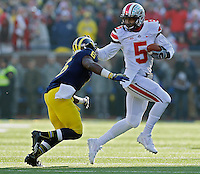Ohio State Buckeyes quarterback Braxton Miller (5) tries to get past Michigan Wolverines defensive back Raymon Taylor (6) in the 3rd quarter during their college football game at Michigan Stadium in Ann Arbor, Michigan on November 30, 2013.  (Dispatch photo by Kyle Robertson)