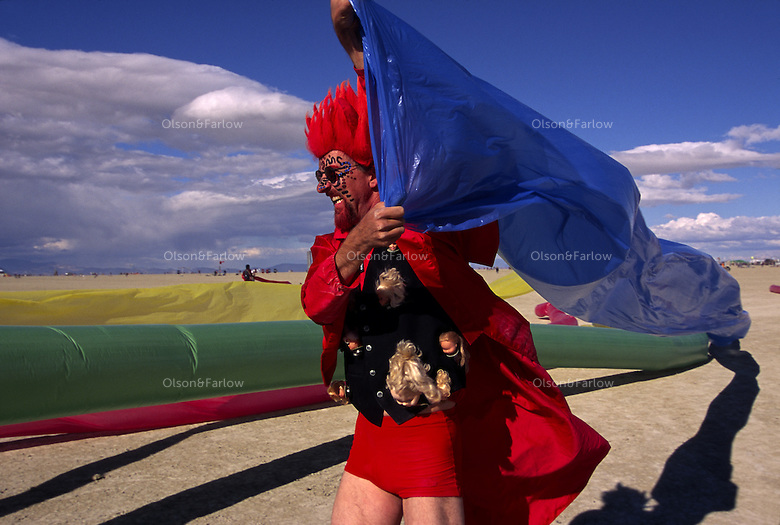 A man catches the wind in a giant tube at the Burning Man Festival. Elaborate, colorful and clever costumes are part of the annual weeklong fest held in Black Rock Desert, northwestern Nevada's Conservation area. For the week of Burning Man, the counter-culture celebration to art and experience becomes one of Nevada's largest cities, attracting tens of thousand of revelers.