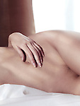 Artistic closeup of a nude woman body lying in bed