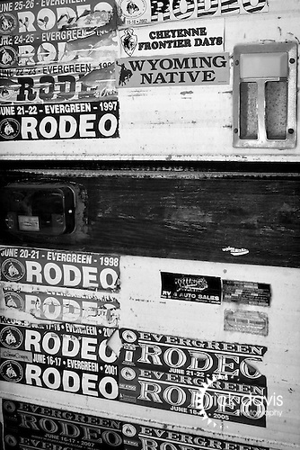 A pickup truck camper sports a collection of rodeo bumper stickers.
