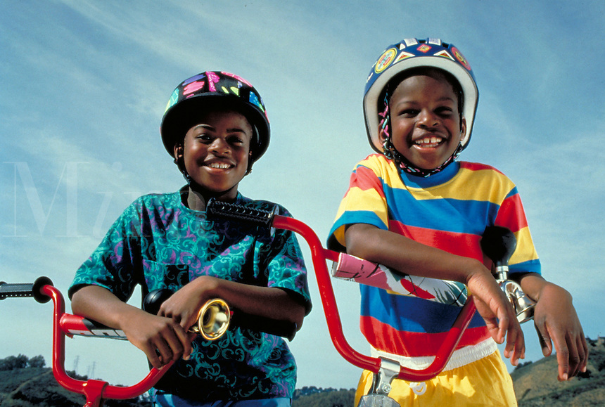 TWO AFRICAN-AMERICAN BOYS READY TO GO CYCLING. WEARING SAFETY GEAR. TWO AFRICAN-AMERICAN BOYS. OAKLAND CALIFORNIA.