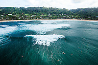 An aerial view of surfers and large waves on the North Shore of O'ahu.