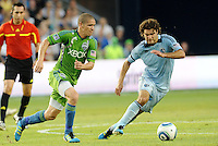 Graham Zusi (8) midfielder Sporting KC moves away from Osvaldo Alonso (6) midfielder Seattle Sounders... Sporting Kansas City were defeated 1-2 by Seattle Sounders at LIVESTRONG Sporting Park, Kansas City, Kansas.