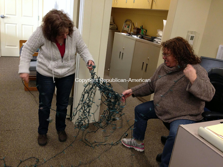 WOODBURY, CT - 3 Jan 2014 - Office Manager Karen Blanchet, left, and Director of Elderly Services Loryn Ray, right, untangle the Christmas lights before storing them until next year. Rick Harrison Republican-American