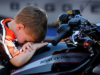 Mar 15, 2014; Gainesville, FL, USA; Declan Hines , son of NHRA pro stock motorcycle rider Andrew Hines (not pictured) lays on his dads motorcycle in the pits during qualifying for the Gatornationals at Gainesville Raceway Mandatory Credit: Mark J. Rebilas-USA TODAY Sports