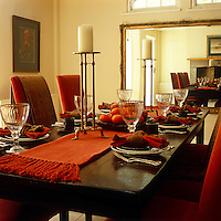 An autumnal setting has been createed with deep red and brown tones in this dining room