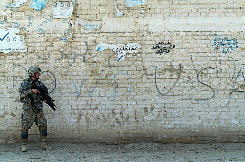 A soldier with the 82nd Airborne patrols the mean streets of Baghdad, Iraq where there are threats in the wall graffiti. (James J. Lee / Army Times)