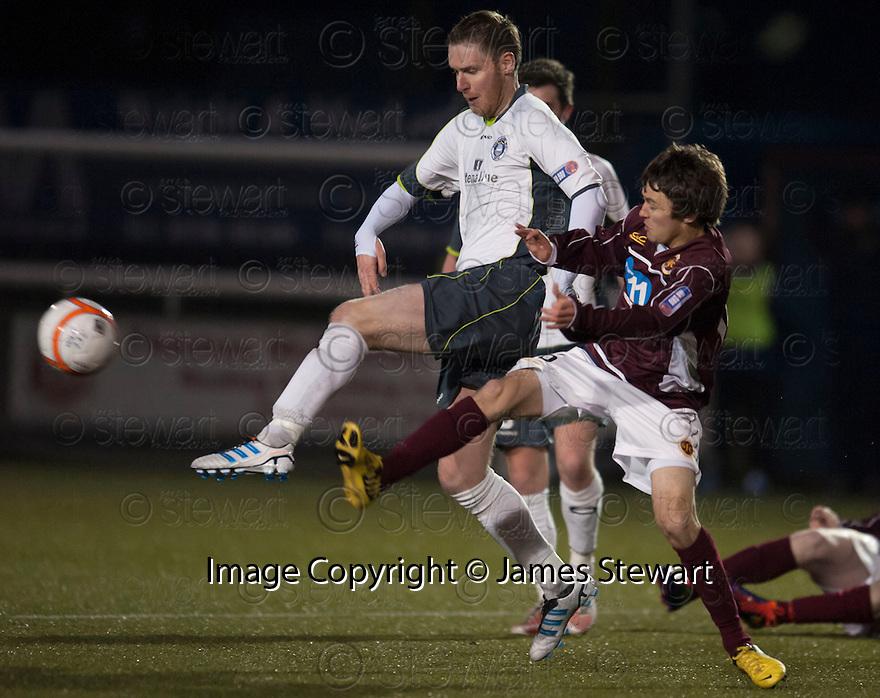 Stranraer's Chris Aitken and Stenny's Jamie Reid challenge for the ball.