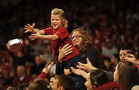 NWA Media/ANDY SHUPE - Scout Norwood, 7, of Fayetteville reaches to catch a pizza as her father, Matt Norwood, holds her up dying a time out in the University of Arkansas men's basketball game with Northwestern State Sunday, Dec. 28, 2014, in Bud Walton Arena in Fayetteville.