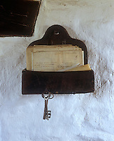 A bunch of keys hangs from a rustic wall-mounted shelf displaying a collection of documents on a wall of the living area