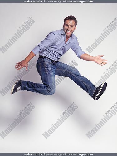 Happy jumping young man wearing jeans and a shirt isolated on gray background