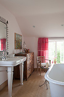 Pink dyed Moroccan sheets used as curtains add a splash of colour to the en suite bathroom