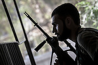 An opposition fighter sniper shot back to a Syrian army sniper whom is hidden at the top levels of a building at Bastan Basha residential neighborhood in the hub of Aleppo City.