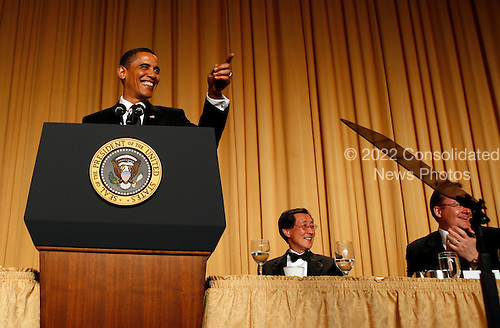 Washington, DC - May 9, 2009 -- United States President Barack Obama gestures toward an audience member as he speaks at the annual White House Correspondents' Association (WHCA) gala dinner at the Washington Hilton Hotel, Washington, DC, Saturday, May 9, 2009. Also shown are Ed Chen, incoming WHCA president (center), and White House Press Secretary Robert Gibbs..Credit: Martin H. Simon - Pool via CNP