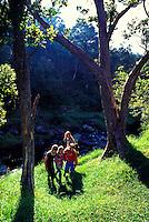 Group of four girls walking near stream at Kokee National Park on Kauai