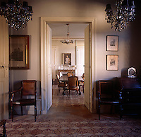 Two wooden chairs stand at either side of a pair of double doors, which lead to  dining room beyond. The room has two chandeliers and a tiled floor.
