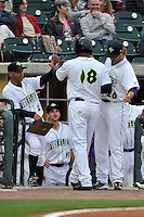 Hitting coach Joel Fuentes (12) of the Columbia Fireflies congratulates center fielder Ivan Wilson (18) who scored the team's first run in the home opener against the Greenville Drive on Thursday, April 14, 2016, the team's first day at the new Spirit Communications Park in Columbia, South Carolina. The Mets affiliate moved to Columbia this year from Savannah. Columbia won, 4-1. (Tom Priddy/Four Seam Images)