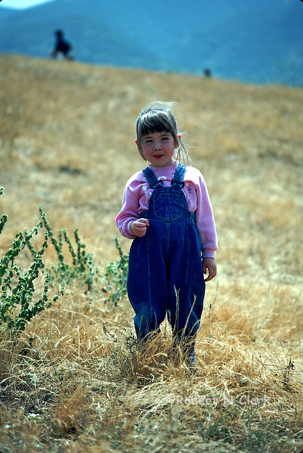 Young girl standing in field wearing jumber smiling