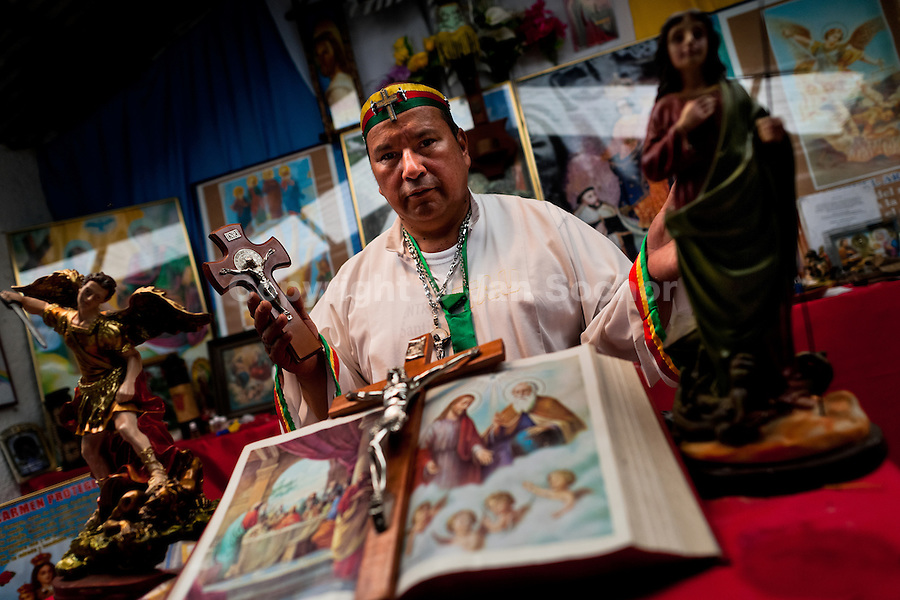 Hermes Cifuentes, a Colombian spiritual healer, prays at an altar in his apartment before performing a ritual of exorcism in La Cumbre, Colombia, 28 May 2012. Exorcism is an ancient religious practice of evicting spirits, generally called demons or evil. Although the formal catholic rite of exorcism is rarely seen and must be only conducted by a designated priest, there are many pastors and preachers in Latin America performing exorcism ceremonies. The 52-year-old Brother Hermes, as the exorcist calls himself, claims to have been carrying out the healing rituals for more than 20 years. Using fire, dirt, candles, flowers, eggs and other natural-based items, in conjunction with Christian religous formulas, he attempts to drive the supposed evil spirit out of a victim's mind and body.