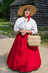 Old Bethpage, New York, USA. August 30, 2015. JANET DEMAREST is the Storyteller of local Long Island Legends during the Old Time Music Weekend at Old Bethpage Village Restoration. Demarest carried a woven straw basket and wore a large brim straw sun hat, blouse with lace trim, and long red hoop skirt in the style of the mid 19th Century.
