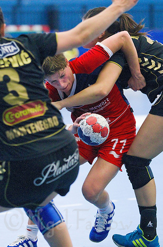 30 MAY 2012 - LONDON, GBR - Lyn Byl (GBR) of Great Britain (centre, in red and blue) looks for a way through the Montenegro defence during the women's 2012 European Handball Championship qualification match at the National Sports Centre in Crystal Palace, Great Britain (PHOTO (C) 2012 NIGEL FARROW)