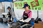 Vendors prepare freshly roasted pieces of seaweed wrap (nori or kim)