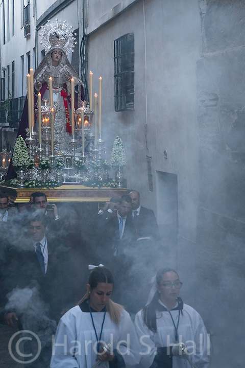 This was a Saturday procession of the Aurora Reina de Madre del Albazin in Granada.  (Aurora Queen Mother)  As best I could tell this very heavy platform, carried by 18 men was an offering or tribute from one near-by church to the other.  She was carried a distance of about two blocks and back.  Solemn music was played during the march.