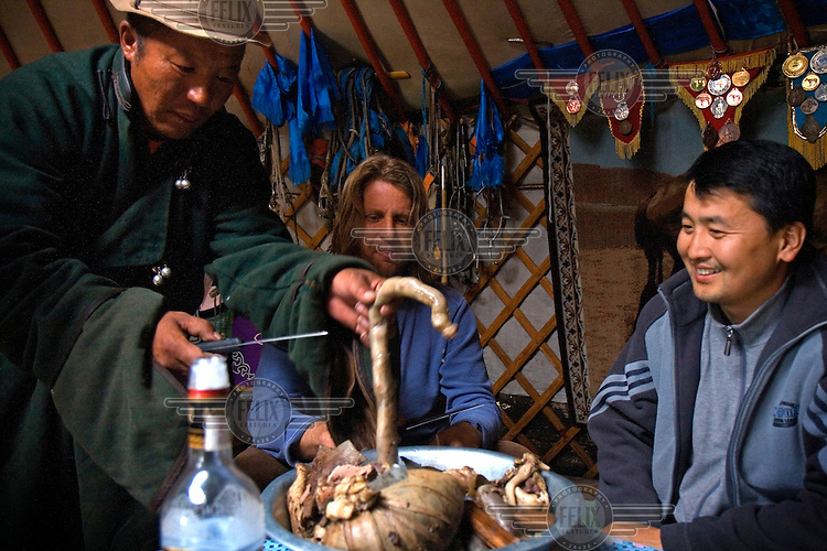 "Rupert Issacson, a campaigning writer and former horse trainer, prepares to eat a meal of sheep's innards in a ger (yurt) during a horseback expedition across Mongolia with his five-year-old autistic son. Rowan, who has been nicknamed ""The Horse Boy"", embarked on a therapeutic journey of discovery with his parents to visit a succession of shaman healers in one of the most remote regions in the world. Following Rowan's positive response to a neighbour's horse, Betsy, and some reaction to treatment by healers, Rowan's parents hoped that the Mongolian shamanistic rituals along the route and the prolonged contact with horses would help to unlock their son's autism and assist his development.."