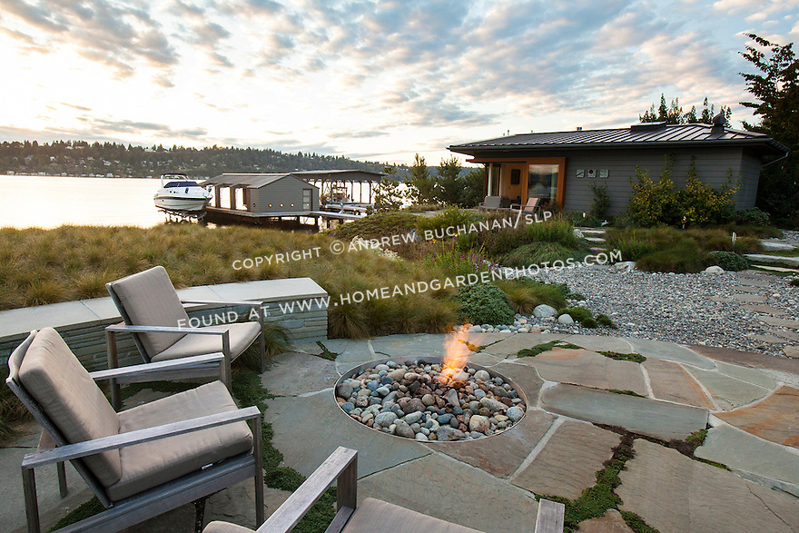 A circular firepit carved into the stone patio of a waterfront home