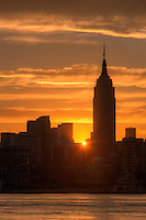 The rising sun shines between Manhattan buildings including the Empire State Building just after sunrise.