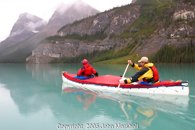 Trent and Linda Enzsol paddle their Clipper Prospector in the rain on Maligne Lake in Jasper National Park, Alberta, Canada.