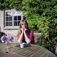 The owner of the house photographed at the garden table in front of a flourishing wisteria trained against the wall behind