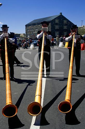 Nr St Bernard, Switzerland. Three men playing on alpen horns.