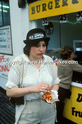 BLACKPOOL TEEN GIRL LOOKING DEPRESSED EATING BAG OF CHIPS WEARING A NOVELTY SOUVENIR SEX APPEAL HAT 1980