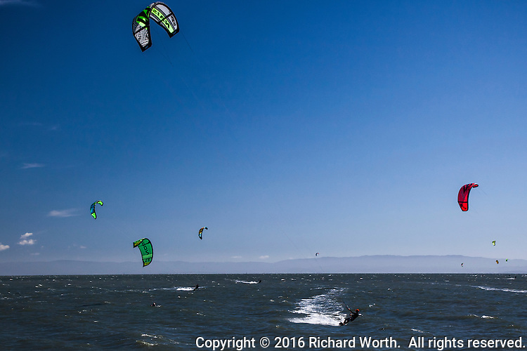 Kiteboarding on San Francisco Bay - One stands out, lower just right of center, his path drawn by the white wake left behind.