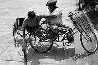Tor Chanta is helping Sompeak to get out of her weelchair race, Battambang, Cambodia-2008
