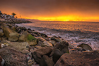 Fine Art Landscape Photograph of a warm golden sunset along the rugged ocean shoreline in Puerto Vallarta Mexico.