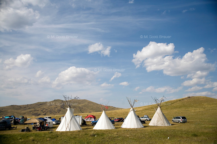 Teepees stand in a field near cars on the Rocky Boy Reservation in northern Montana, USA.