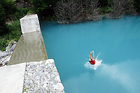 A man jumps into a turquoise lake in the Jiuzhaigou National Park. Sichuan Province. China.