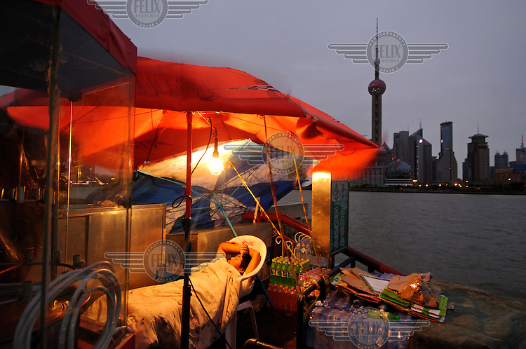 A sleeping sentinel at his stall on the Bund, decorated with an awning advertising Coca-Cola, as dawn breaks with Pudong financial district across the Huangpu Rier behind.