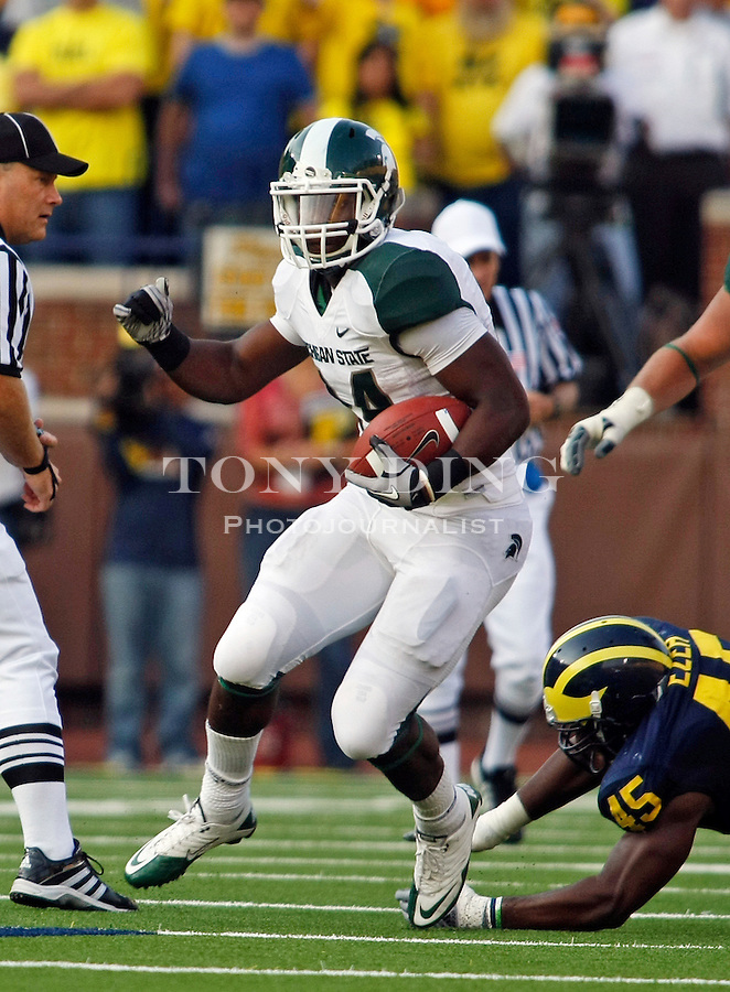 Michigan State running back Le'Veon Bell (24) escapes a tackle from Michigan linebacker Obi Ezeh (45) in the third quarter of an NCAA college football game, Saturday, Oct. 9, 2010, in Ann Arbor. Michigan State won 34-17. (AP Photo/Tony Ding)