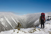 A hiker takes in the view of Hellgate Ravine from the summit of Bondcliff in the Pemigewasset Wilderness in the New Hampshire White Mountains during the winter months. Bondcliff, Mount Bond, and West Bond were named in 1876 for Professor G.P. Bond of Harvard University.
