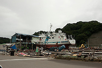 A landscape view of a boat on land and a damaged building at Miyako Bay during reconstruction efforts following the 311 Tohoku Tsunami in Miyako, Japan  © LAN