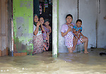 Women and children look out of their house during November 2014 flooding in Meulaboh in Indonesia's Aceh province. Flooding in the region has grown worse because of climate change and the proliferation of palm oil plantations.