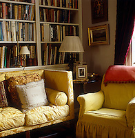 A yellow damask sofa and a comfortable matching armchair in the corner of the living room beside the bookcase