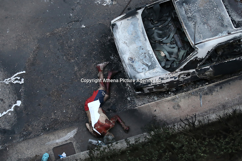 Pictured: The body of a man lies next to burned cars in the Mati area, Kokkino Limanaki near Rafina, Greece. Tuesday 24 July 2018<br /> Re: Deaths caused by wild forest fires throughout Greece.