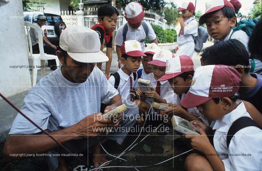 INDONESIA Jakarta, business idea, Nintendo games hired by street vendor, kids playing Nintendo gameboy connected with battery / INDONESIEN Jakarta, Schulkinder in Schuluniform spielen Nintendo gameboy bei einem Strassenverleiher vor der Schule, die Nintendos sind mit einer Autobatterie verkabelt