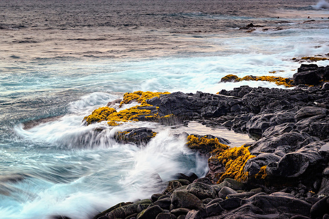 surf flowing over lava rocks in Kona, Hawaii