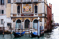 Italy, Venice. Gondolas in front of an old building on Canal Grande.